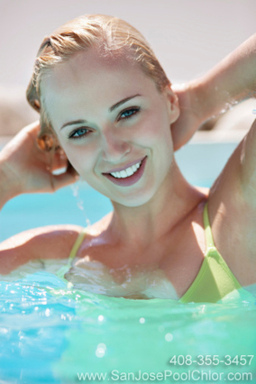 Pretty blonde girl looking at you from the swimming pool maintained by San Jose Pool Chlor example